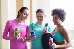 Glückliche Frauen mit Flaschen und Smartphone in der Turnhalle stockbild