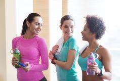 Glückliche Frauen mit Flaschen Wasser in der Turnhalle Stockfoto