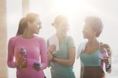 Glückliche Frauen mit Flaschen Wasser in der Turnhalle Stockfotografie