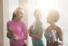 Glückliche Frauen mit Flaschen Wasser in der Turnhalle Stockbild