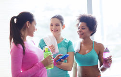 Glückliche Frauen mit Flaschen Wasser in der Turnhalle Lizenzfreie Stockfotos