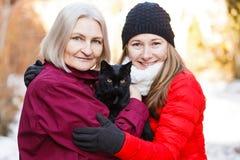 Glückliche Frauen und die schwarze Katze Stockfotografie