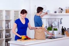 Glückliche Frau und junger Mann, die Lebensmittelgeschäfte auspackt Lizenzfreies Stockfoto