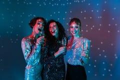 Glückliche Frauenaufstellung lokalisiert mit den Discoballlichtern, die Gläser mit Champagner halten lizenzfreie stockbilder