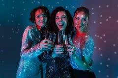 Glückliche Frauenaufstellung lokalisiert mit den Discoballlichtern, die Gläser mit Champagner halten stockfotografie