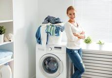 Glückliche Frauenhausfrau in der Waschküche nahe dem waschenden machi lizenzfreies stockbild