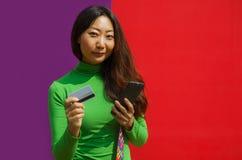 Glückliche Frauenholding Kreditkarte und Smartphone auf buntem Hintergrund stockfotografie