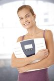Glückliche Frauenholdingskala in den Armen Lizenzfreies Stockfoto