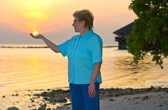 Glückliche Frauenholdingsonne auf Strand Lizenzfreie Stockfotos