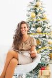Glückliche Frauenlesezeitschrift nahe Weihnachtsbaum stockfotografie