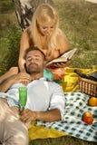 Glückliche Frauenlesung für gutaussehenden Mann nach Picknick Lizenzfreies Stockfoto