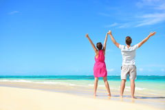 Glückliche freie Paare, die am Strandreisefeiertag zujubeln