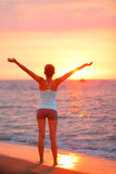 Glückliche Freiheitsfrau, die bei Strandsonnenuntergang sich entspannt Lizenzfreie Stockfotografie