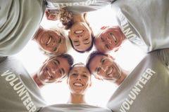 Glückliche freiwillige Familie, die unten der Kamera betrachtet Stockfoto