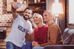 Glückliche freiwillige selfies mit Pensionären stockfotografie
