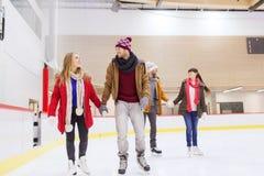 Glückliche Freunde auf Eisbahn Stockfoto