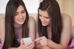 Glückliche Freunde in den Pyjamas, die Smartphone auf Bett betrachten Stockbild