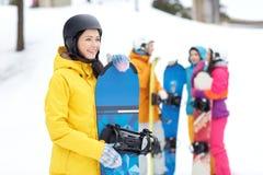 Glückliche Freunde in den Sturzhelmen mit Snowboards lizenzfreie stockfotos