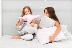 Glückliche Freunde der Mädchen mit netten Kissen Kissenschlachtpyjamapartei Sleepoverzeit für Kissenschlacht Handeln was auch imm lizenzfreies stockbild