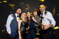 Glückliche Freunde an der Partei unter Konfettis über Schwarzem lizenzfreies stockfoto