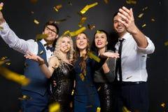 Glückliche Freunde an der Partei unter Konfettis über Schwarzem stockbilder