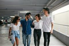Glückliche Freunde in der zufälligen modernen Kleidung am Mall-Parken lizenzfreie stockfotos