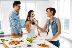 Glückliche Freunde, die Abendessen-Haus haben Essen des Lebensmittels, Freundschaft Stockfoto