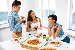 Glückliche Freunde, die Abendessen-Haus haben Essen des Lebensmittels, Freundschaft lizenzfreies stockfoto