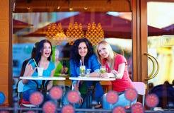 Glückliche Freunde, die auf Caféterrasse sitzen Stockfotos
