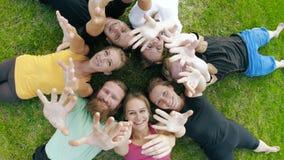 Glückliche Freunde, die auf Gras und wellenartig bewegenden Händen liegen stock video footage