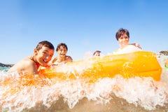 Glückliche Freunde, die auf Luftmatraze schwimmen stockfotos