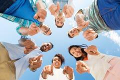 Glückliche Freunde, die auf Sie stehend im Kreis zeigen stockfotos