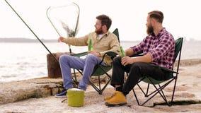 Glückliche Freunde, die Bier auf Pier fischen und trinken stock footage