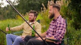 Glückliche Freunde, die Bier auf See fischen und trinken stock footage