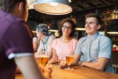 Glückliche Freunde, die Bier trinken und an der Bar sprechen Stockbild