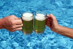 Glückliche Freunde, die Bier trinken und Gläser klirren Lizenzfreie Stockfotos