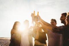 Glückliche Freunde, die Bierflaschen anheben lizenzfreie stockfotografie