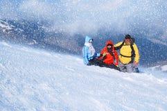 Glückliche Freunde, die den Spaß draußen spielt im Schnee haben Schöne Schneefälle Lizenzfreie Stockbilder