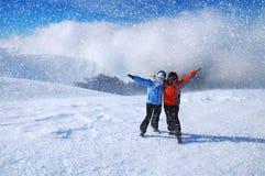 Glückliche Freunde, die den Spaß draußen spielt im Schnee haben Schöne Schneefälle Lizenzfreies Stockbild