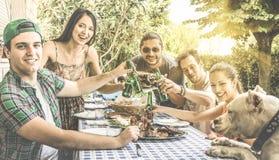 Glückliche Freunde, die den Spaß zusammen isst und röstet an bbq haben lizenzfreies stockbild