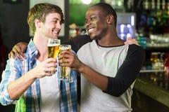 Glückliche Freunde, die etwas trinken Stockbild