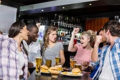 Glückliche Freunde, die etwas trinken und Sport aufpassen Lizenzfreies Stockbild
