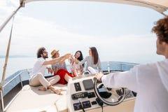 Glückliche Freunde, die Gläser Champagner klirren und auf Yacht segeln stockfoto