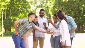 Glückliche Freunde, die Hände im Park stapeln stock video footage