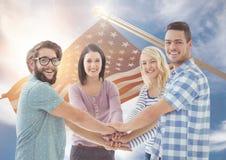 Glückliche Freunde, die ihre Hände zusammen mit einer flatternden amerikanischen Flagge in Hintergrund einsetzen Lizenzfreie Stockfotos