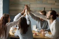 Glückliche Freunde, die im Café gibt hoch fünf für Freundschaft sich treffen stockfoto