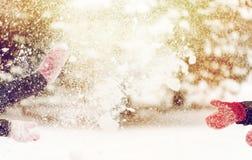 Glückliche Freunde, die mit Schnee im Winter spielen Stockbild