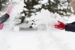 Glückliche Freunde, die mit Schnee im Winter spielen Stockfotos
