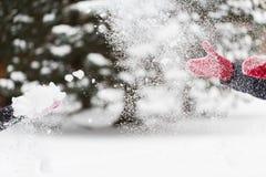 Glückliche Freunde, die mit Schnee im Winter spielen Stockfotografie