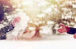 Glückliche Freunde, die mit Schnee im Winter spielen Lizenzfreie Stockfotografie